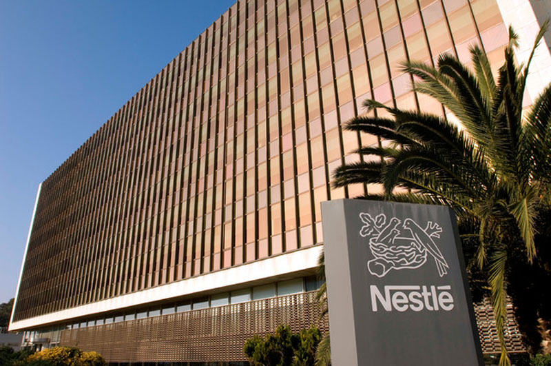 Façana de l'Edifici I de la Central de Nestlé Espanya, a Esplugues de Llobregat, cedida per la companyia el 26 d'octubre del 2015. Pla general de l'edifici i, en primer terme, el tòtem amb el logotip de Nestlé. (Horitzontal)